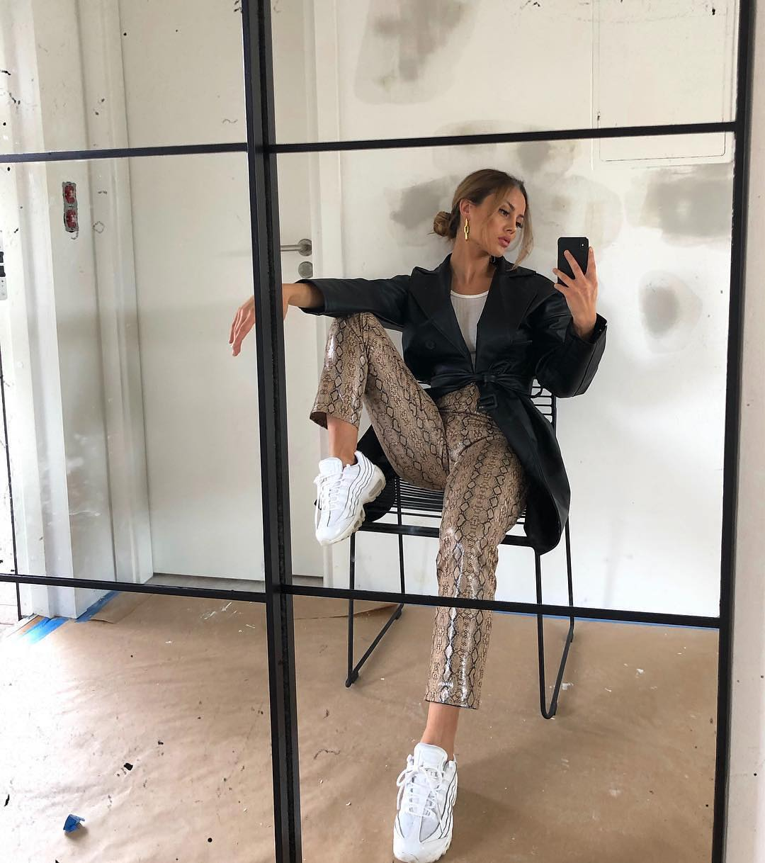 Black leather trench coat, snakeskin print pants and white ugly sneakers for fall 2021