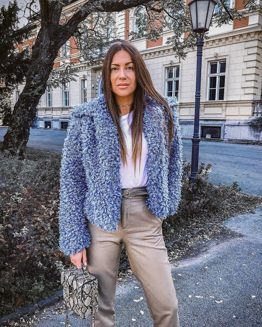 Blue faux fur jacket with a white top and gray trousers for fall 2021