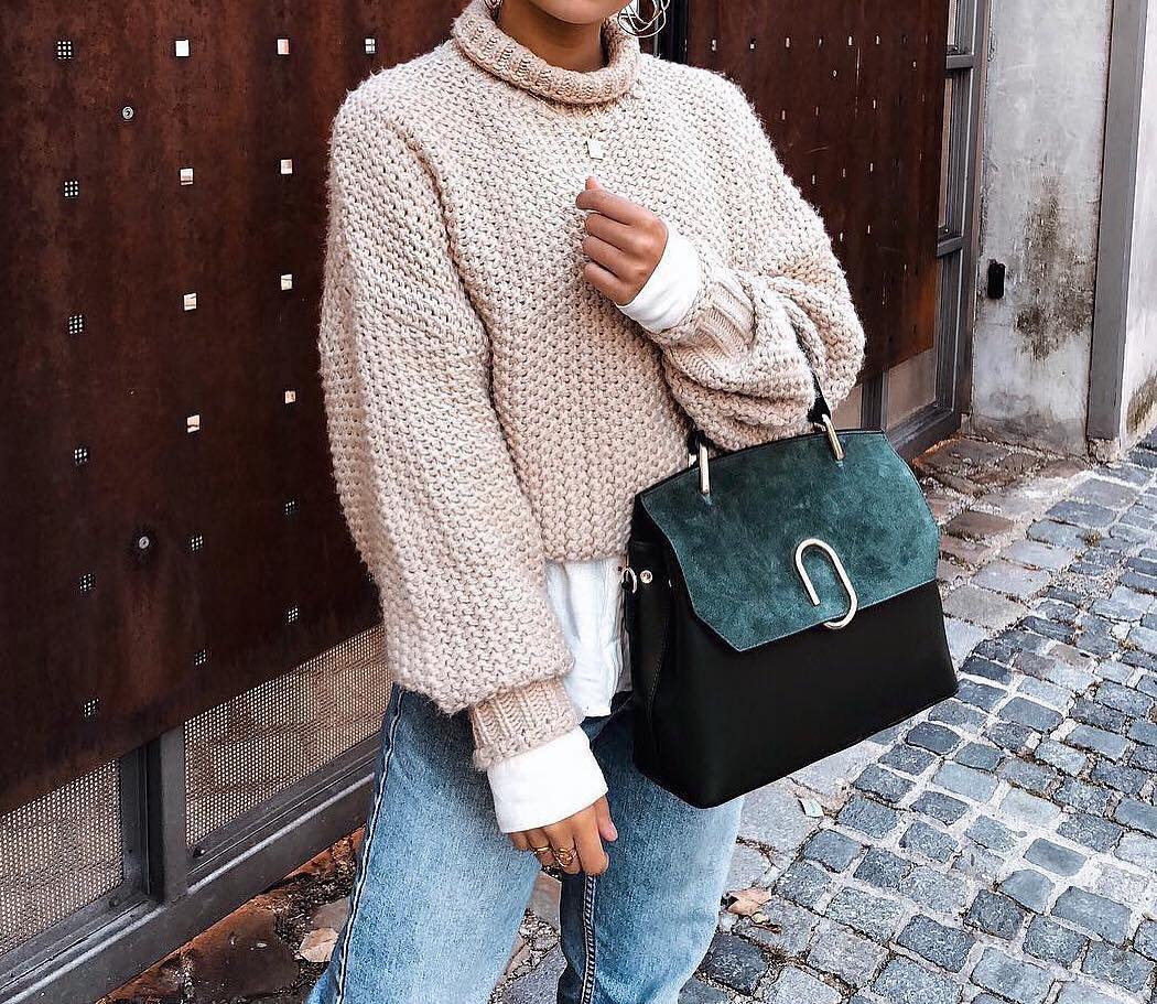 Oversized blush sweater with a white top and blue jeans for fall 2021