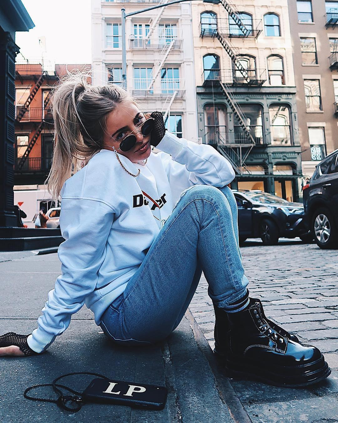 Patent combat boots, white sweatshirt and jeans for casual street hikes 2021